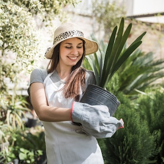 Smiling young woman wearing hat holding black pot plant in hands