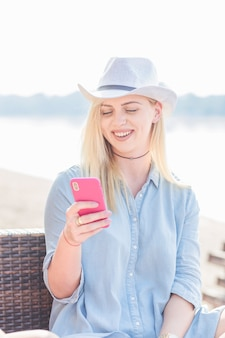 Smiling young woman wearing hat holding mobile phone