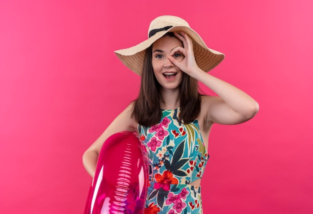 Sorridente giovane donna che indossa il cappello che tiene l'anello di nuotata e che fa segno giusto sulla parete rosa isolata