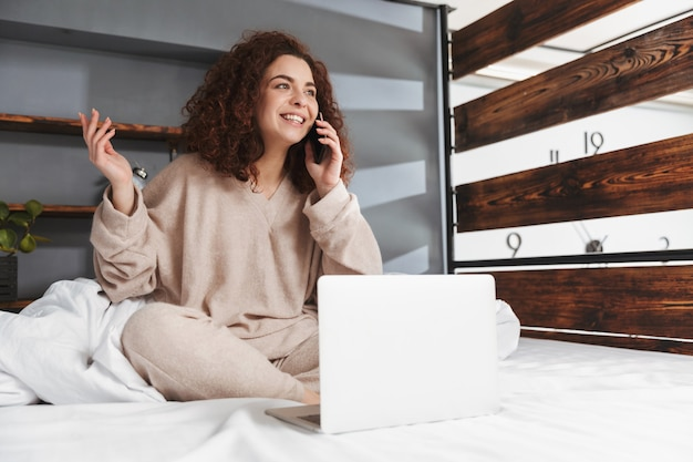 Smiling young woman wearing house clothes using laptop and cellphone while sitting in bed on white linen at home
