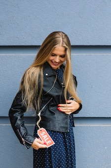 Усмехаясь кожаная куртка молодой женщины нося смотря бирку продажи
