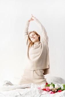 朝のベッドでストレッチパジャマを着て笑顔の若い女性