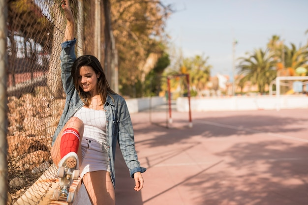 Smiling young woman wearing roller skate sitting near the fence of outdoor court