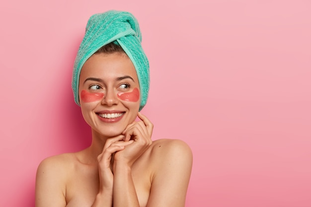 Smiling young woman wears cosmetic moisturizing patches under eyes, removes wrinkles, cares about complexion, wears soft towel on head, has cosmetics procedure