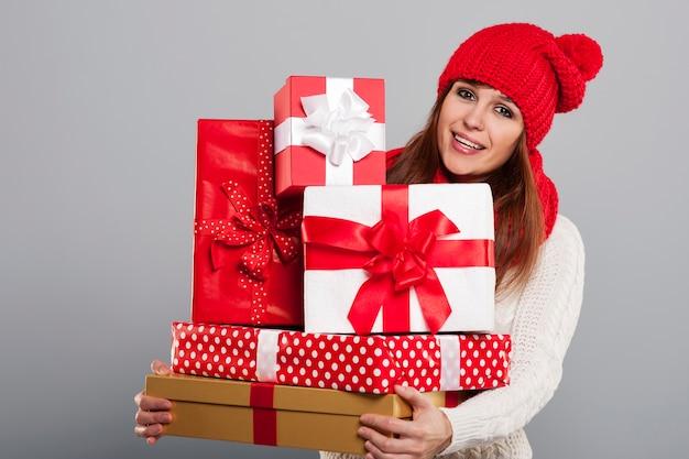 Giovane donna sorridente in cappello di inverno che tiene molti regali di natale