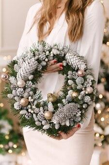 クリスマスツリーの近くにクリスマスリースと笑顔の若い女性