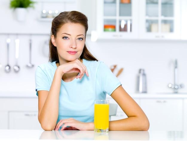新鮮なオレンジジュースのガラスと笑顔の若い女性