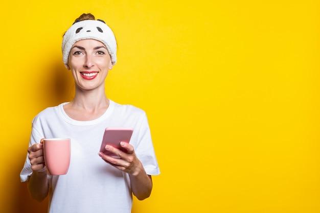 電話と黄色の背景にコーヒーのカップを持つ若い女性を笑顔