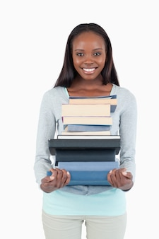 Smiling young woman with a pile of books against a white background