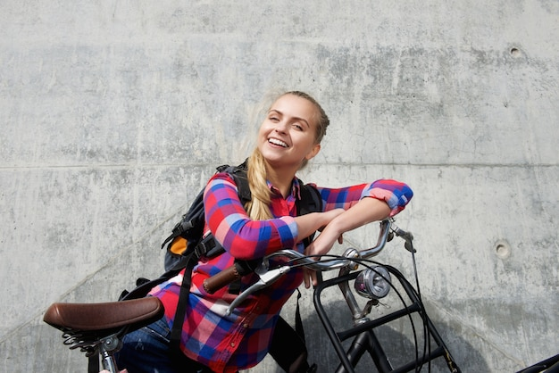 Smiling young woman with backpack and bike