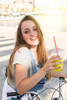 Smiling young woman with bicycle holding glass of juice