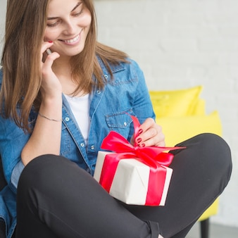 Smiling young woman with birthday gift talking on cellphone