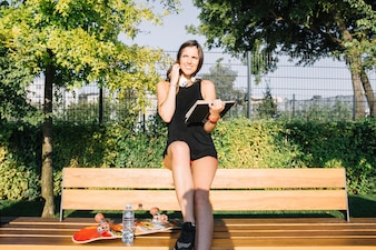 Smiling young woman with book sitting on bench in park