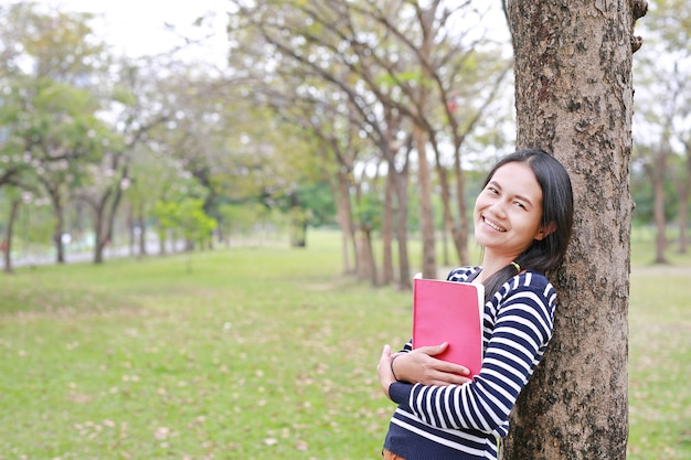 Smiling young woman with book standing lean against trunk tree in summer park outdoor.