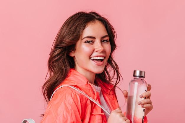 水のボトルで笑顔の若い女性が正面を見る