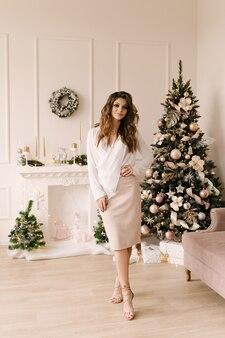 クリスマスツリーの近くにクリスマスプレゼントボックスと笑顔の若い女性