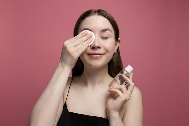 눈을 감고 웃고 있는 젊은 여성이 면 패드로 화장을 지우고 분홍색 배경에 미셀라 물 한 병을 들고 있습니다. 여자 청소 얼굴입니다. 치료 및 미용. 뷰티 루틴, 스킨케어