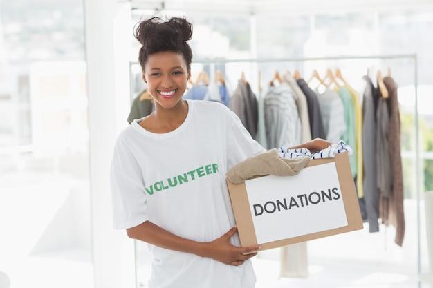 Улыбается молодая женщина с пожертвованием одежды