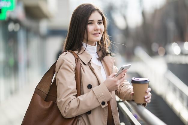 市内の電話でコーヒーカップを持つ若い女性を笑顔