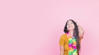 ピンクの背景に立ってカラフルな偽の花輪で若い女性に笑顔