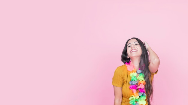 Smiling young woman with colorful fake garland standing against pink background