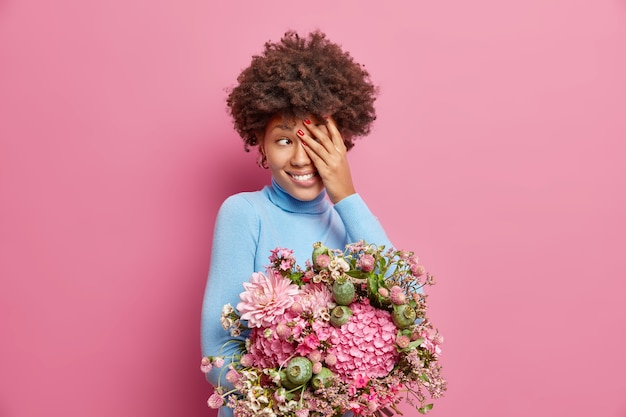 Smiling young woman with curly hair covers face and looks away gladfully holds bouquet of flowers received from beloved person enjoys spring time isolated over pink wall