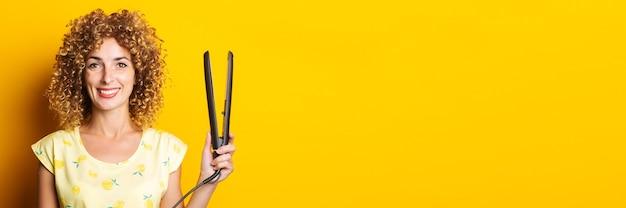 黄色の背景にストレートヘアアイロンを保持している巻き毛を持つ若い女性の笑顔。