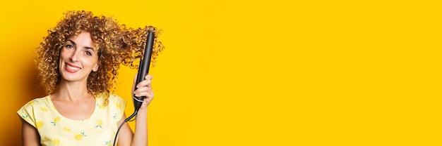 巻き毛の若い女性の笑顔は、黄色の背景にストレートヘアアイロンで髪をまっすぐにします。