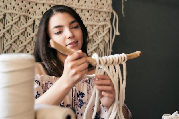 マクラメの装飾を保持している暗い茶色の髪の若い女性の笑顔