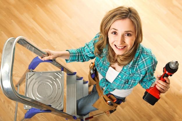 Улыбающаяся молодая женщина с дрелью и лестницей