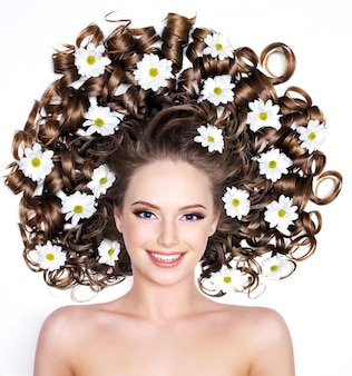 Smiling young woman with flowers in long hair on white