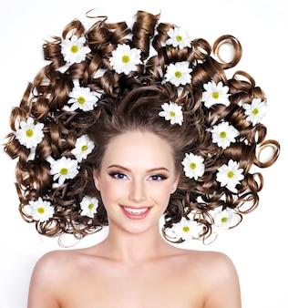 Sorridente giovane donna con fiori nei capelli lunghi su bianco