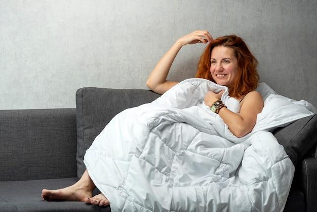 白いカバーの下に横たわっている生姜髪の若い女性の笑顔。遊び心のある視線。ベッドで休んでいる若い女性。