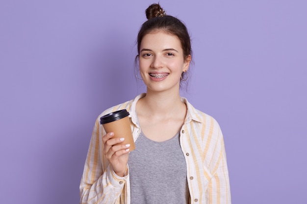 Smiling young woman with hair bun holding take away coffee in hands