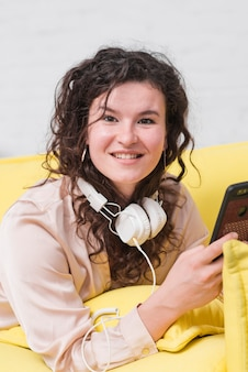Smiling young woman with headphone around her neck holding mobile phone