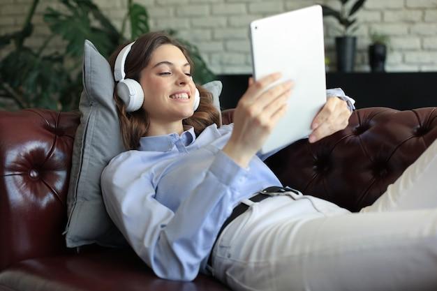 헤드폰과 소파에 디지털 태블릿을 들고 웃고 있는 젊은 여성.