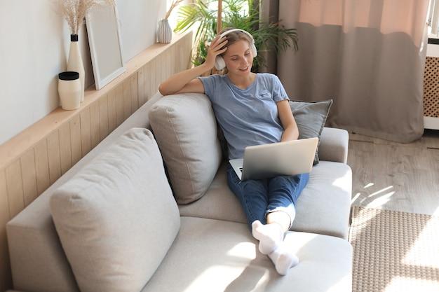 헤드폰과 소파에 노트북을 들고 웃는 젊은 여자.