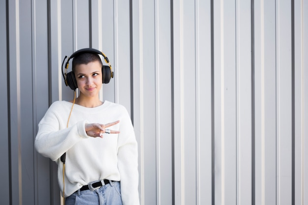 Smiling young woman with headphones and bob hairstyle gesturing peace sign