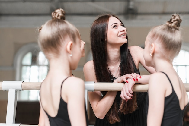 Smiling young woman with her ballerina students in dance class