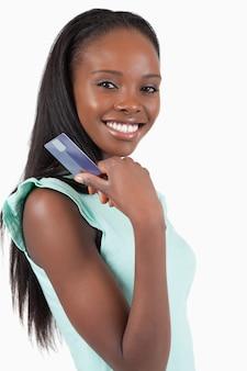Улыбается молодая женщина с ее кредитной карты на белом фоне