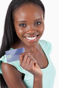 Улыбается молодая женщина с ее новой кредитной карты