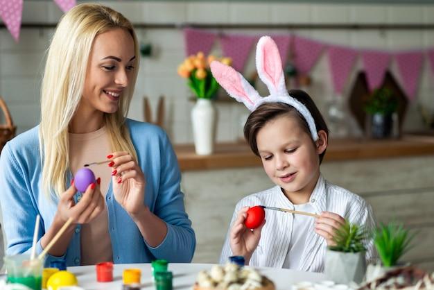 그녀의 아들 페인트 다채로운 계란을 가진 젊은 여자를 웃 고