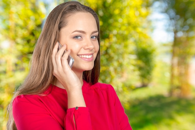 Smiling young woman with mobile phone