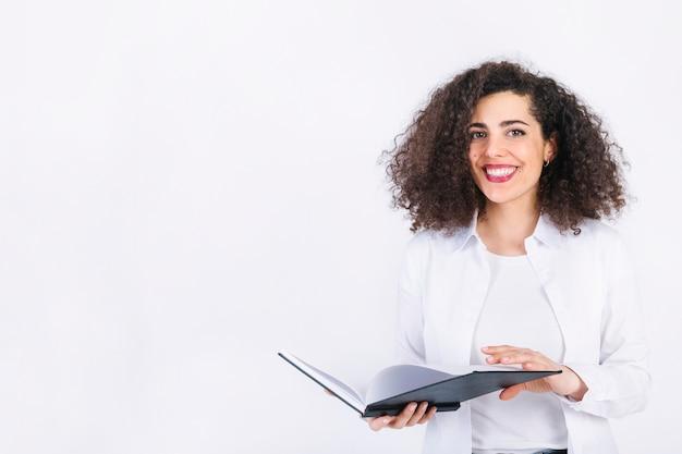 Giovane donna sorridente con il blocco note