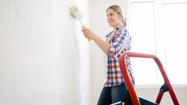 Улыбающаяся молодая женщина с малярным валиком делает ремонт в квартире.