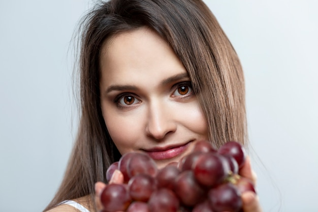 Smiling young woman with purple grapes. beautiful brunette on a gray background.