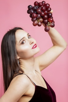 Smiling young woman with purple grapes. beautiful brunette on a pink background.