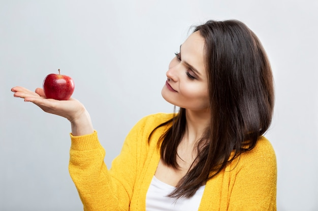 Smiling young woman with red apple. beautiful brunette in a yellow sweater on a gray background.