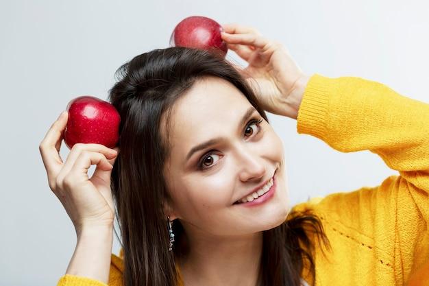 赤いリンゴと笑顔の若い女性。健康的な食事と菜食主義。