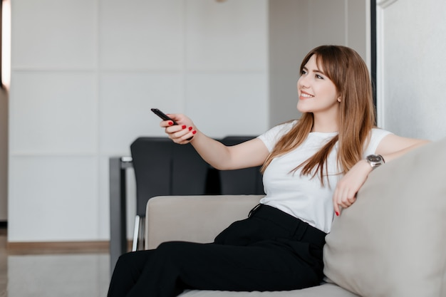 Smiling young woman with remote control from tv sitting on a couch at home in apartment
